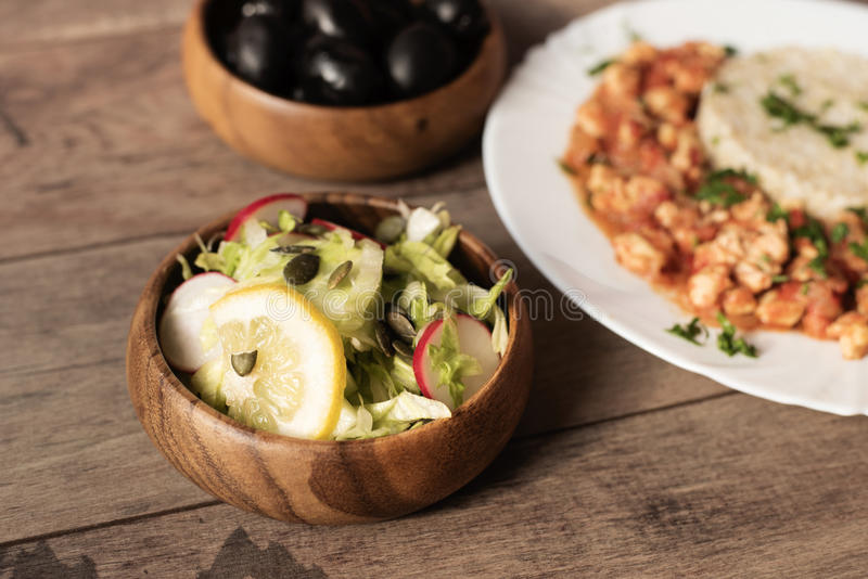 Green iceberg lettuce salad with cucumbers, radishes, sunflower seeds, lemon and parmesan. Behind, in defokus chicken with rice stock image