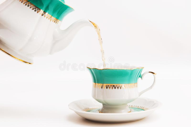Green indian cup of tea and kettle on white background. Isolated on white. Indian dishes stock image
