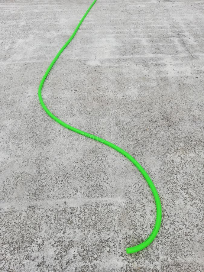 Green irrigation hose on a reinforced concrete slab. Ready to water the concrete to avoid cracking stock images