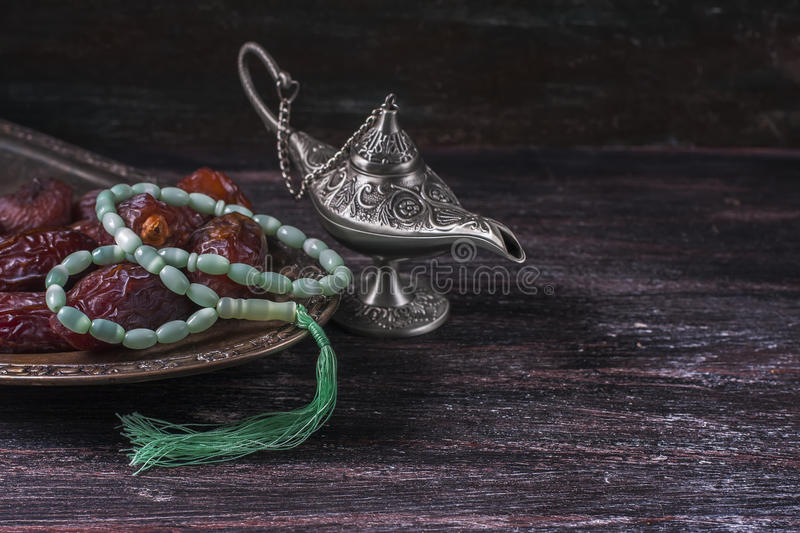 Green islamic prayer beads, dates and silver aladdin`s lamp on a dark wooden background. Ramadan concept. Selective focus royalty free stock photography