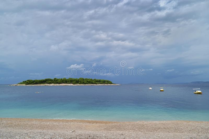 A green island in the azure sea. Beach, boats and cloudy sky. Primosten, Croatia, royalty free stock photo