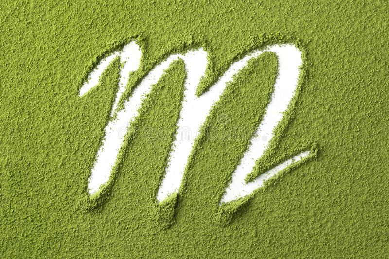 Green Japanese Matcha tea powder full frame and the letter M. Close up royalty free stock photo