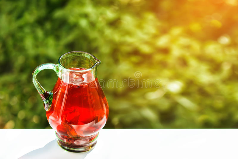 Green jar of cranberry lemonade. Outdoor. Shallow depth of field. Sunlight green bokeh in background. Focused on upper part of jar royalty free stock image