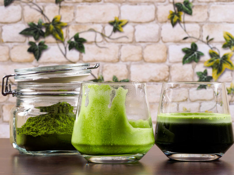 Green juice. Two glasses of green juice, one full and one empty, plus one jar of green juice powder, set over a wenge board, with a background of brick wall and stock photography