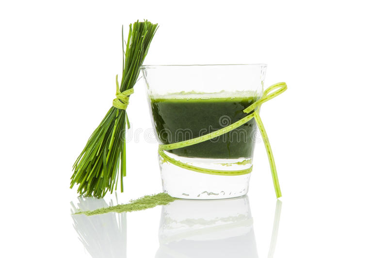Green juice. Green wheat grass juice, barley grass blades and ground powder on white background. Natural herbal medicine, living healthy stock photo