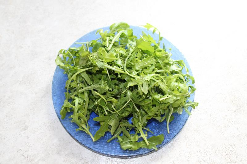 Green juicy arugula salad on a beautiful blue plate. stock images