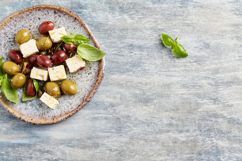 Green and kalamata olives, capers and feta cheese on rustic wooden background. Healthy Snack Idea. T. Op view stock images