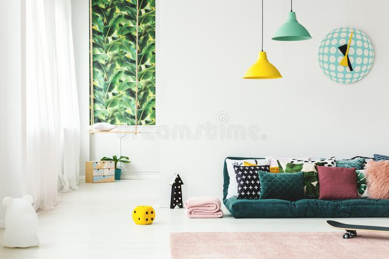 Green kid`s room with clock. Pillows on emerald green mattress in kid`s room interior with swing and clock on white wall royalty free stock image