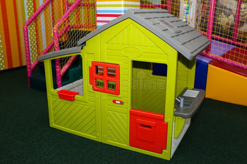 Green kids playhouse in the entertainment center. Plastic children play house with red and orange door and window. Green floor. stock images
