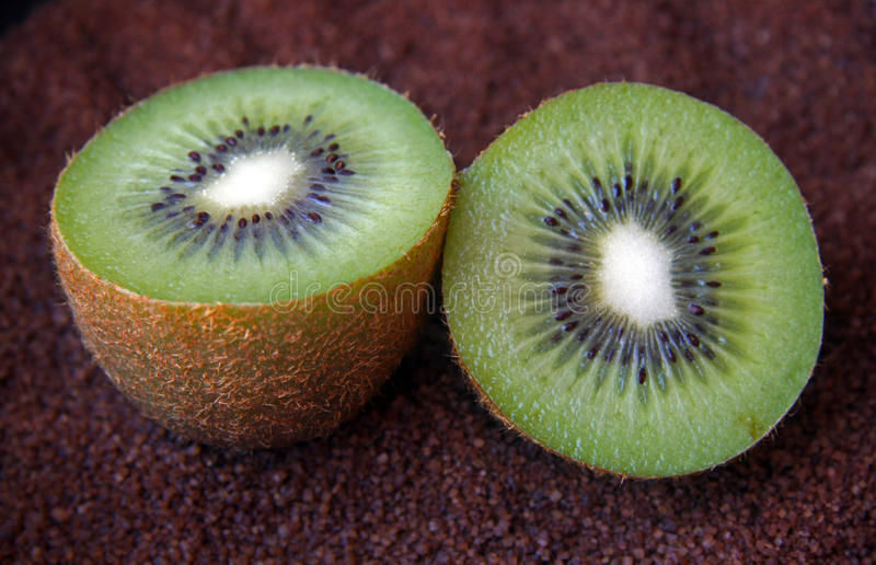 Green kiwi. Detail of the flesh of a green Kiwi divided in two halves on dark bottom stock images