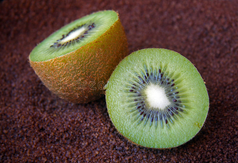 Green kiwi. Detail of the flesh of a green Kiwi divided in two halves on dark bottom stock photo