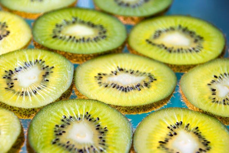 Green kiwi fruit slices on lighted glass. Photograph of some green kiwi fruit slices on lighted glass stock photos