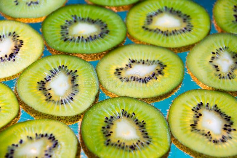 Green kiwi fruit slices on lighted glass. Photograph of some green kiwi fruit slices on lighted glass stock image
