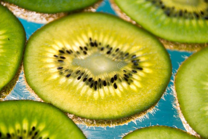 Green kiwi fruit slices on lighted glass. Photograph of some green kiwi fruit slices on lighted glass stock photo