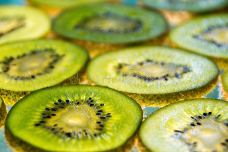 Green kiwi fruit slices on lighted glass. Photograph of some green kiwi fruit slices on lighted glass stock images