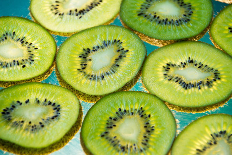 Green kiwi fruit slices on lighted glass. Photograph of some green kiwi fruit slices on lighted glass royalty free stock images