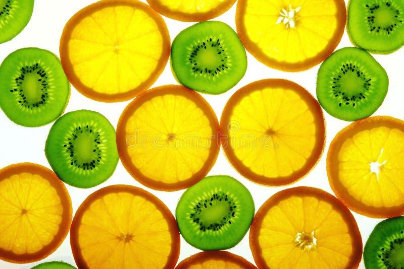 Green kiwi and orange slices. Background stock photography