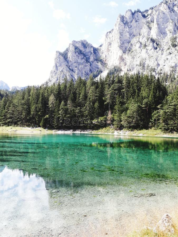 Green lake in Austria sorrounded by trees and Mountains royalty free stock photography