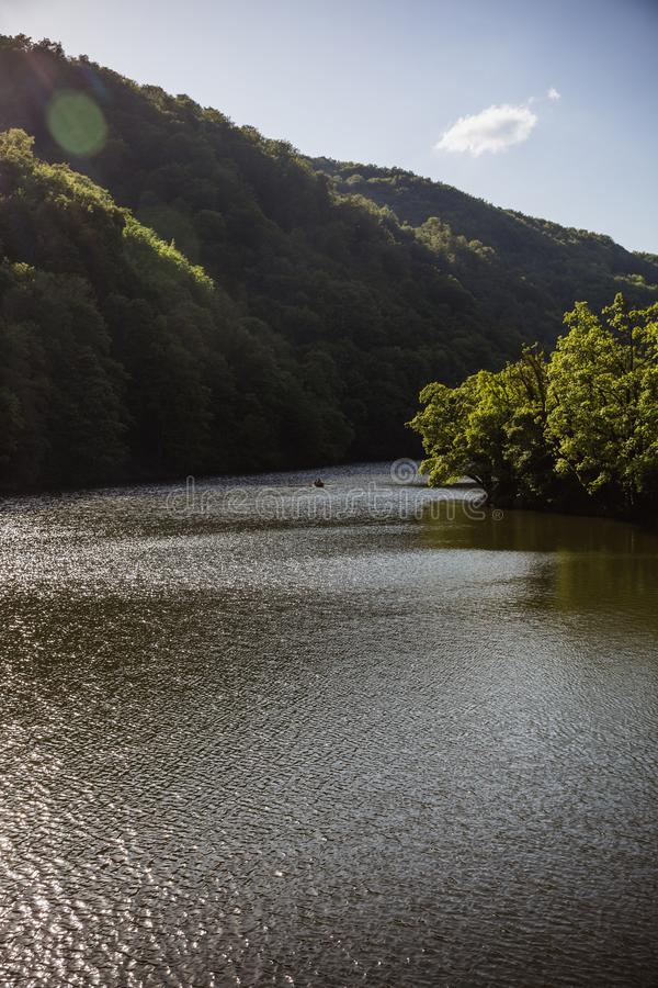 The Green Lake of Hamori in Lillafure near Miskolc, Hungary. Spring landscape with sunrays covering the mountains. The solar path. On the water. Unrecognizable stock photography