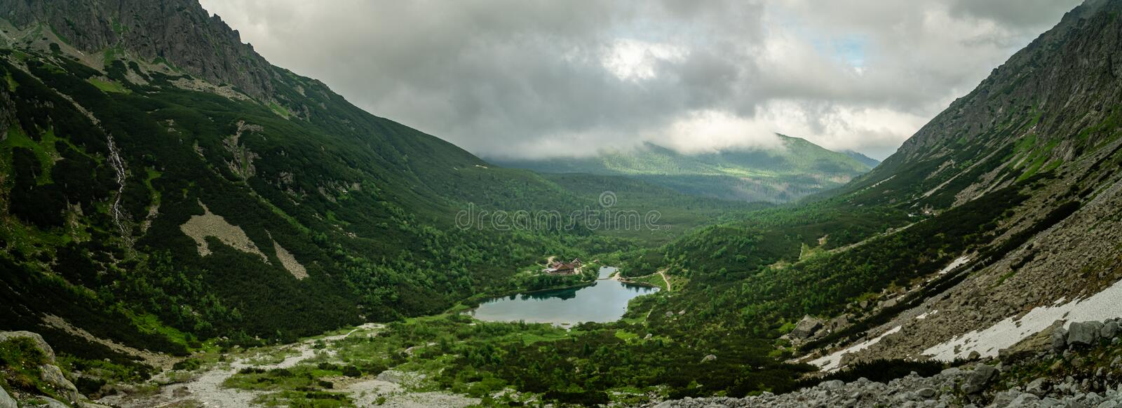Green lake with mountain house in High Tatras valley.  royalty free stock photography