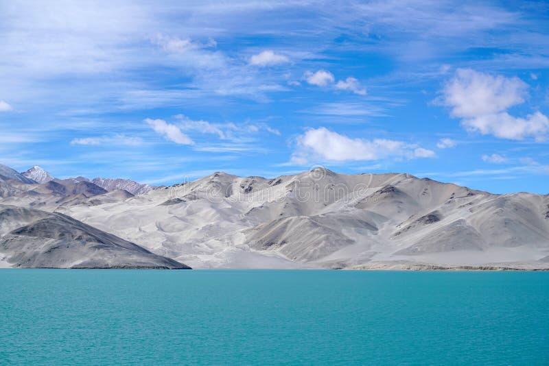 Green lake, snow mountain, white clouds, blue sky royalty free stock photos