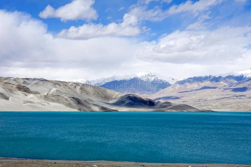 Green lake, snow mountain, white clouds, blue sky in Pamirrs. The beautiful scenery of blue lake, snow mountains, white clouds and blue sky in autumn in Pamirs royalty free stock image