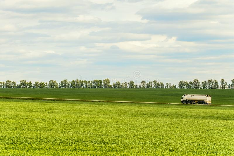 Green landscape with white tank trailer truck stock photos