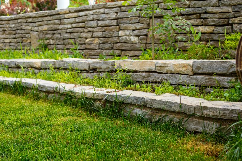 Green lawn and stone path with stone walls stock photo