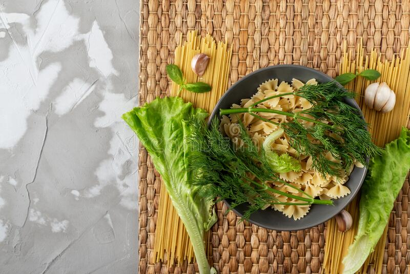 A green leaf of lettuce and sprigs of dill on a gray ceramic plate with pasta on a Mat of dried seaweed and on a concrete textured. Background, top view, space stock photo