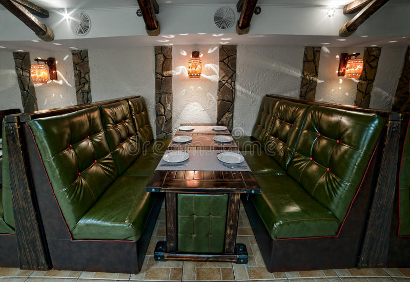 Green leather interior of the pub two sofas, wooden table served. For dinner plates for six people, forks, knives. Light lights on the walls stock images