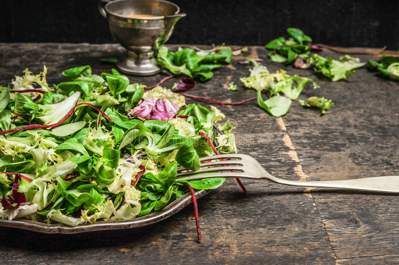 Green leaves mix salad with fork and dressing on rustic kitchen table, close up. Health , detox or diet food stock image