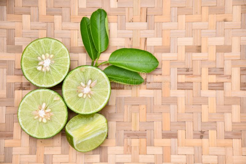 Green lemon cut on a basket. Into the background stock images