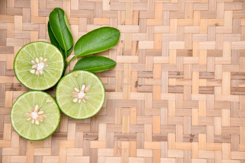 Green lemon cut on a basket stock photography