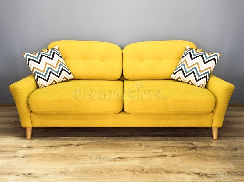 Green lemon yellow sofa with pillow. Soft lemon couch. Modern divan in interior gray wall wooden floor stock photography