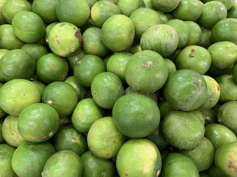 Green lemons selling in the market royalty free stock photo