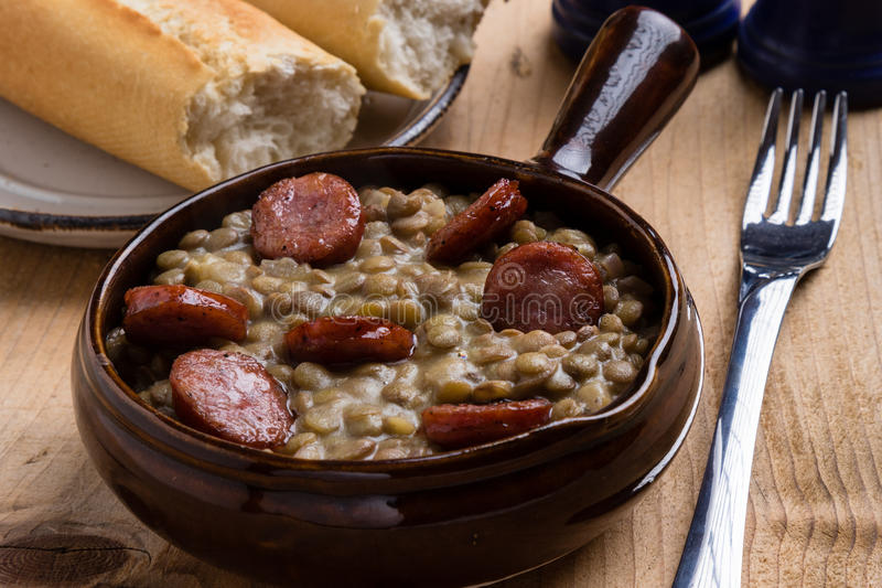 Green lentil stew. With sausage in brown bowl royalty free stock photo