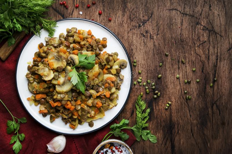 Green lentils with mushrooms and vegetables, old wooden kitchen table background, place for text. Vegetarian meal, vegan food stock image