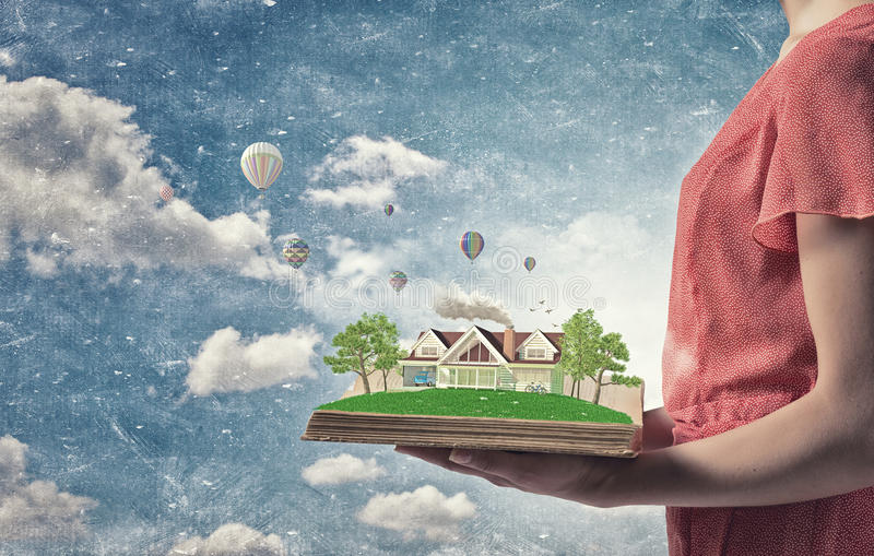 Green life concept. Young woman in red dress holding opened book with house model royalty free stock photography