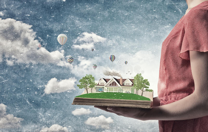 Green life concept. Young woman in red dress holding opened book with house model stock images