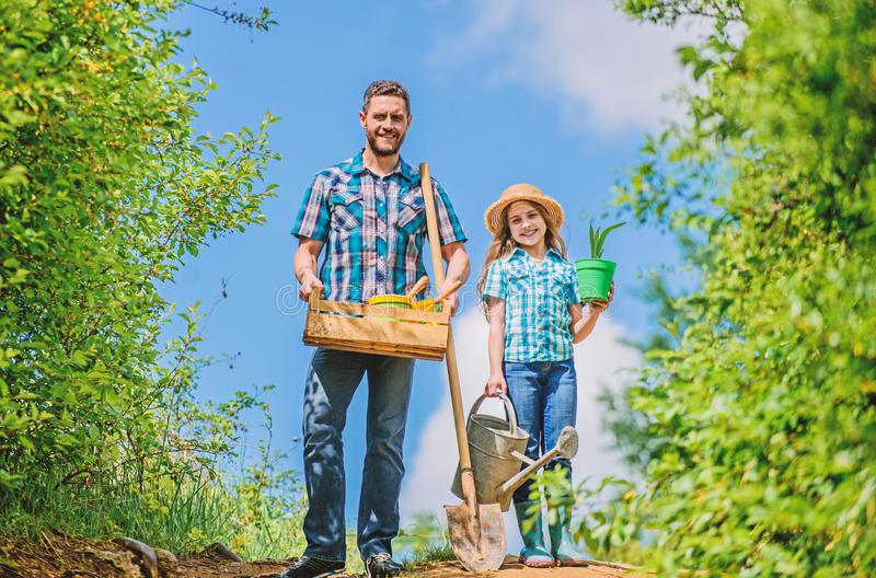 Green life. farmer man with little girl. garden tools, shovel and watering can. kid worker with dad hold box. family stock images