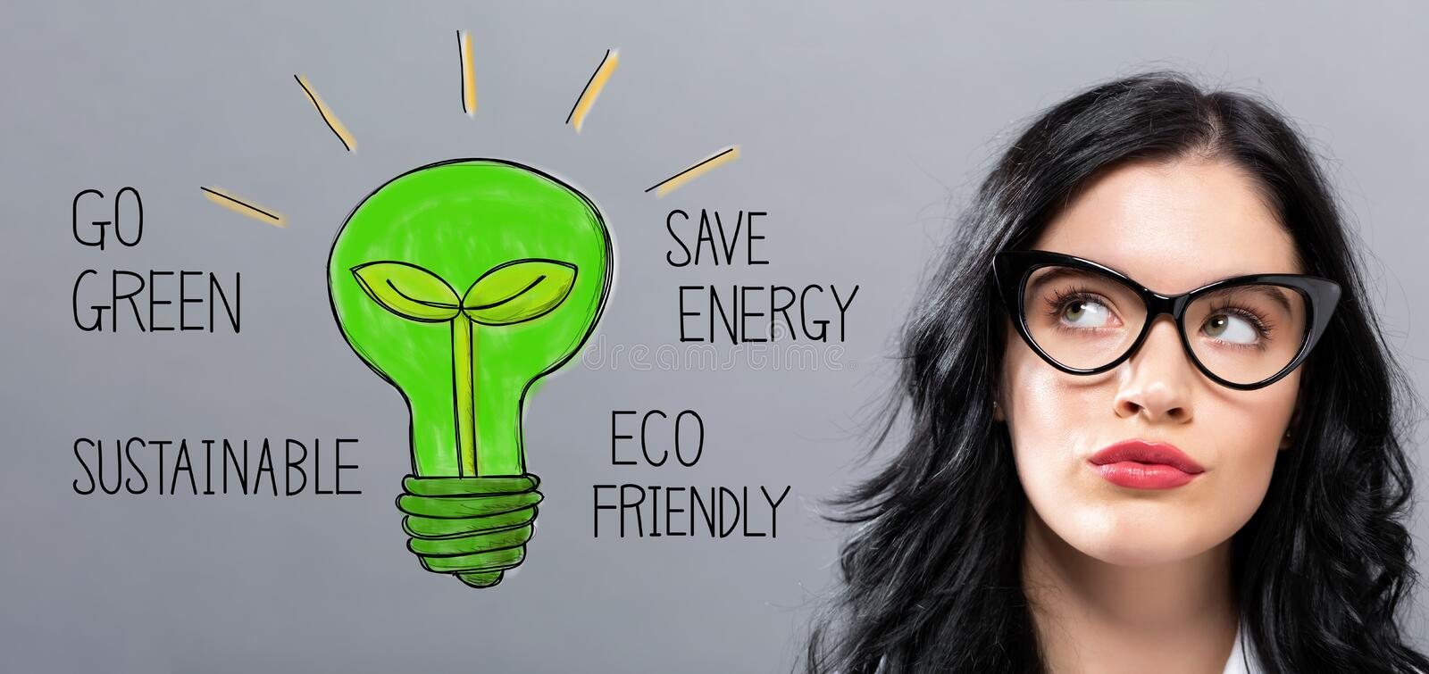 Green Light Bulb with young businesswoman royalty free stock photo