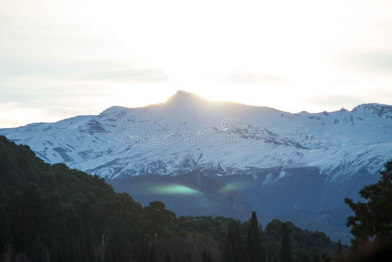 Green light phenomena above Sierra Nevada snowy mountain. Green light phenomena during sunrise above Sierra Nevada snowy mountain. Granada, Spain royalty free stock photo