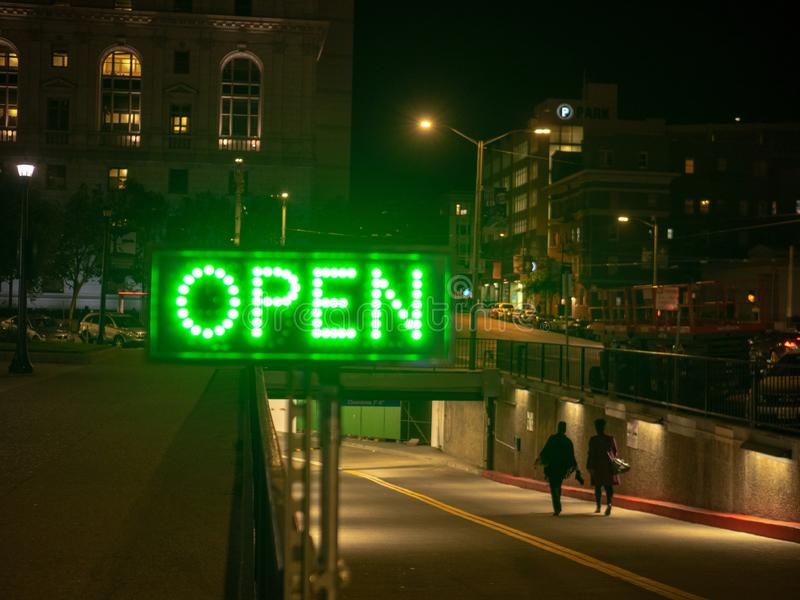 Green lighted open sign in dark city area with people walking in to tunnel. Green lighted open sign in dark city area with people walking into tunnel royalty free stock images