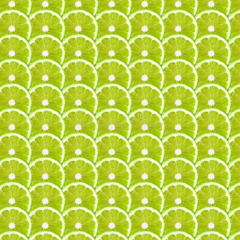 Green lime slices pattern background. Natural symmetrical full frame food texture royalty free stock image