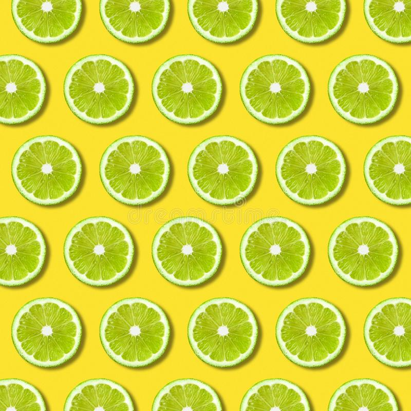 Green lime slices pattern on vibrant yellow color background royalty free illustration