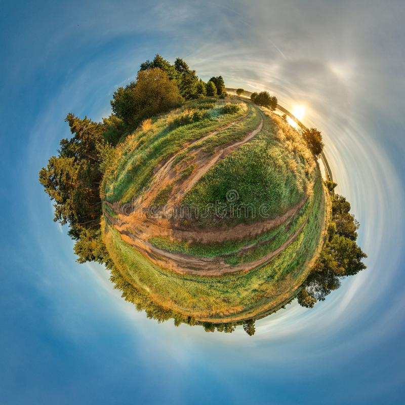 Green little planet with trees and field. Tiny planet with blue sky and sun. 360 viewing angle. stock photos