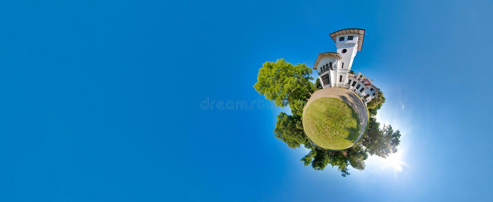 Green little planet with trees, soft blue sky and building. Tiny planet sunset near the castle. 360 viewing angle. stock photos