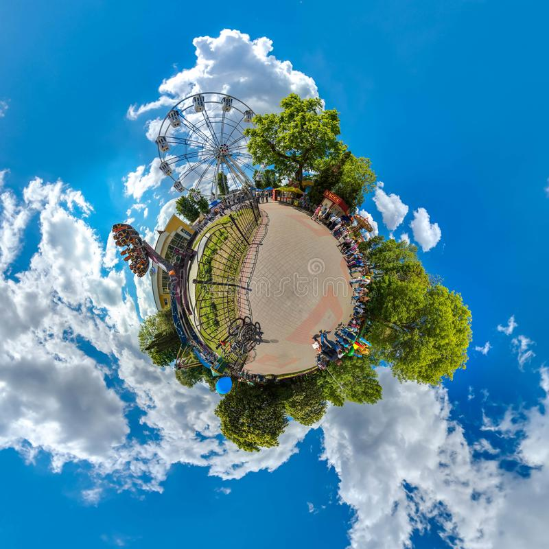 Green little planet with trees, white cluds and soft blue sky. Tiny planet of amusement park. 360 viewing angel. stock photo