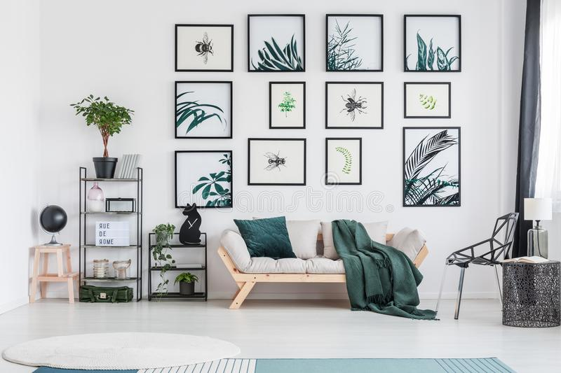 Green living room with sofa. Lamp on metal table next to designer chair in living room with green pillow on grey sofa stock photography