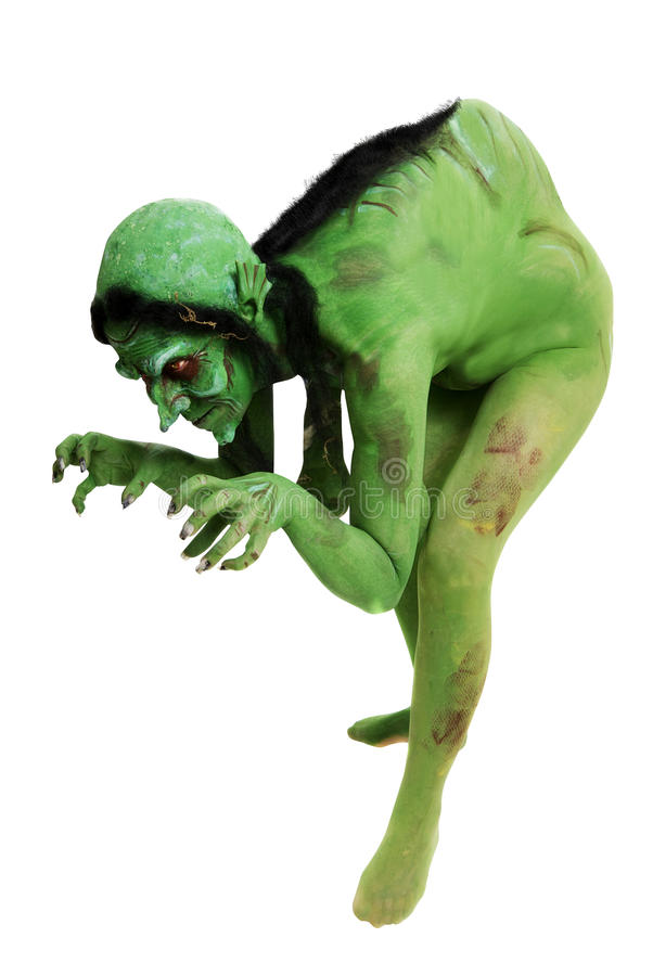 Green looking witch like creature. Witch like creature isolated on a white background bent over posing in a funny but scary fashion stock photo
